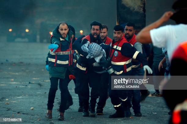 TOPSHOT Palestinian medics evacuate a wounded Palestinian protester during clashes between Israeli troops and Palestinian demonstrators in Ramallah...