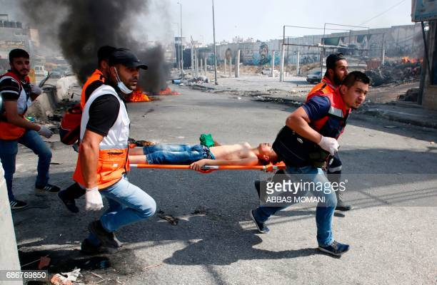 TOPSHOT Palestinian medics evacuate a wounded protester during clashes with Israeli troops following a protest by Palestinians in support of...