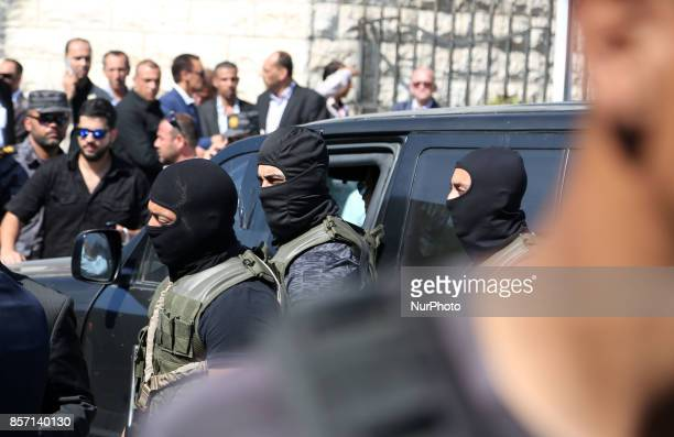A Palestinian member of Hamas security forces and an Egyptian security officer gesture as they stand guard outside the Palestinian cabinet...