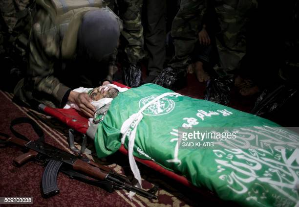 A Palestinian member of the Ezzedine alQassam Brigades the armed wing of the Hamas movement prays over the body of his comrade Marwan Maarouf during...