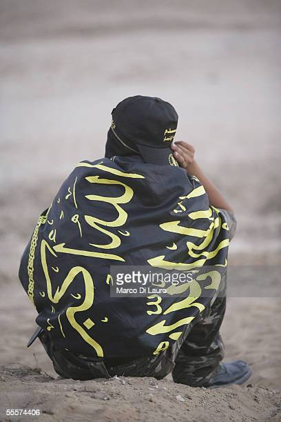 Palestinian member of the Islamic Jihad Militant Movememt sits wrapped in the Islamic Jihad flag at a rally in the Netzarim Settlement on September...