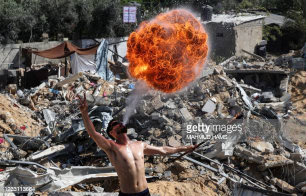Palestinian members of Gaza's Bar Woolf sports team perform with fire above the ruins of a building destroyed in recent Israeli air strikes, in Beit...