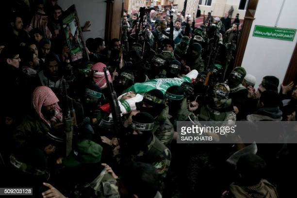 Palestinian members of the Ezzedine alQassam Brigades the armed wing of the Hamas movement carry the body of their comrade Marwan Maarouf during his...