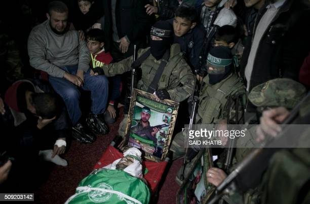 Palestinian members of the Ezzedine alQassam Brigades the armed wing of the Hamas movement pray over the body of their comrade Marwan Maarouf during...