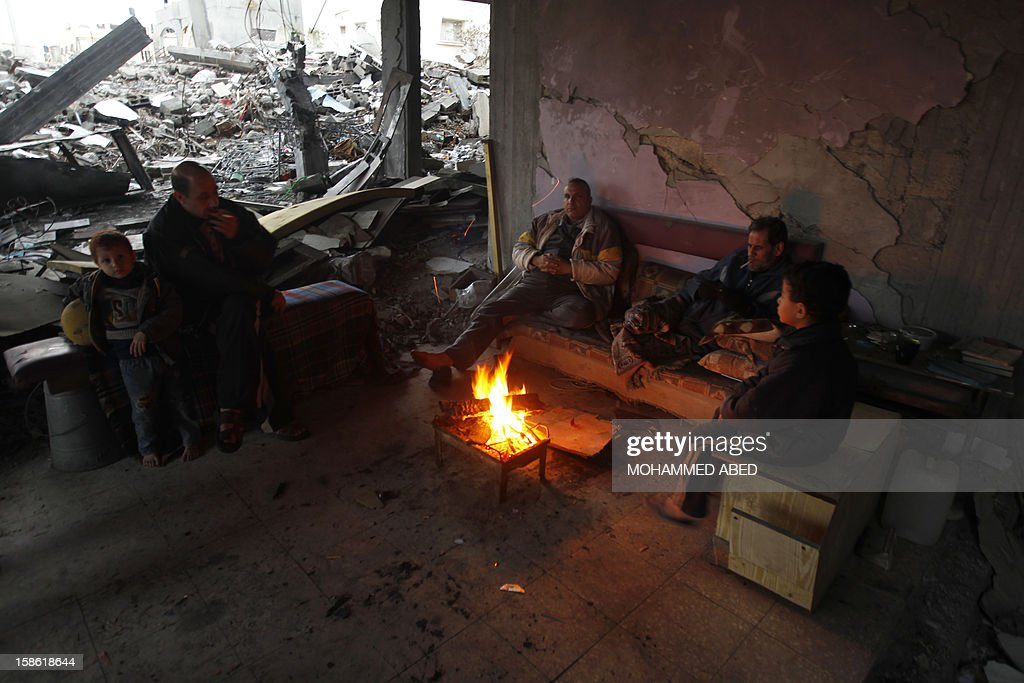 Palestinian men and children warm themselves by a fire inside a building which was damaged during November's eight-day confrontation between Israel and Gaza militants, on December 21, 2012 in Beit Lahia, northern Gaza Strip. The eight-day confrontation claimed the lives of 177 Palestinians, mostly civilians, and six Israelis, medical sources on both sides said.