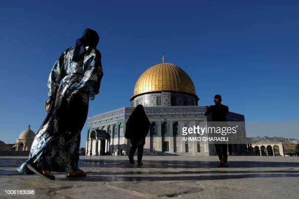 Palestinian men and women walk in front of the Dome of the Rock at the alAqsa mosque compound in the Jerusalem's Old City on July 27 after the site...