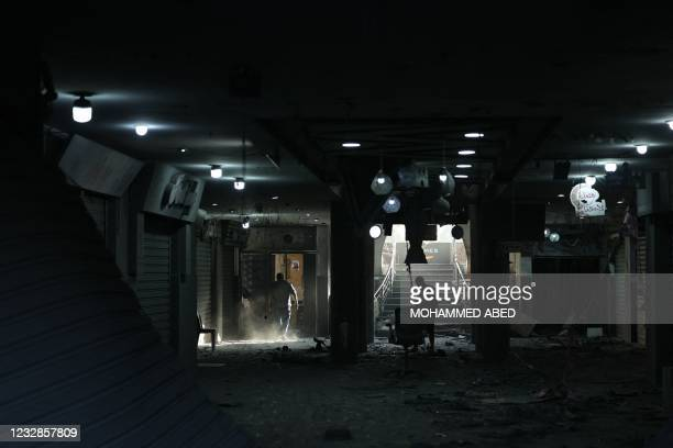 Palestinian men are pictured on May 13, 2021 inside the heavily-damaged Al-Sharouk tower, which housed the bureau of the Al-Aqsa television channel...