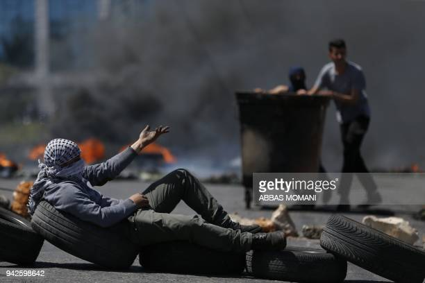 TOPSHOT Palestinian men burn tyres during a protest in the West Bank city of Ramallah on April 6 2018 Clashes erupted on the GazaIsrael border Friday...