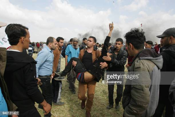 Palestinian men carry a wounded boy after Israeli forces intervene in the Palestinian protests as they gather at Israel's border near Khan Yunis...