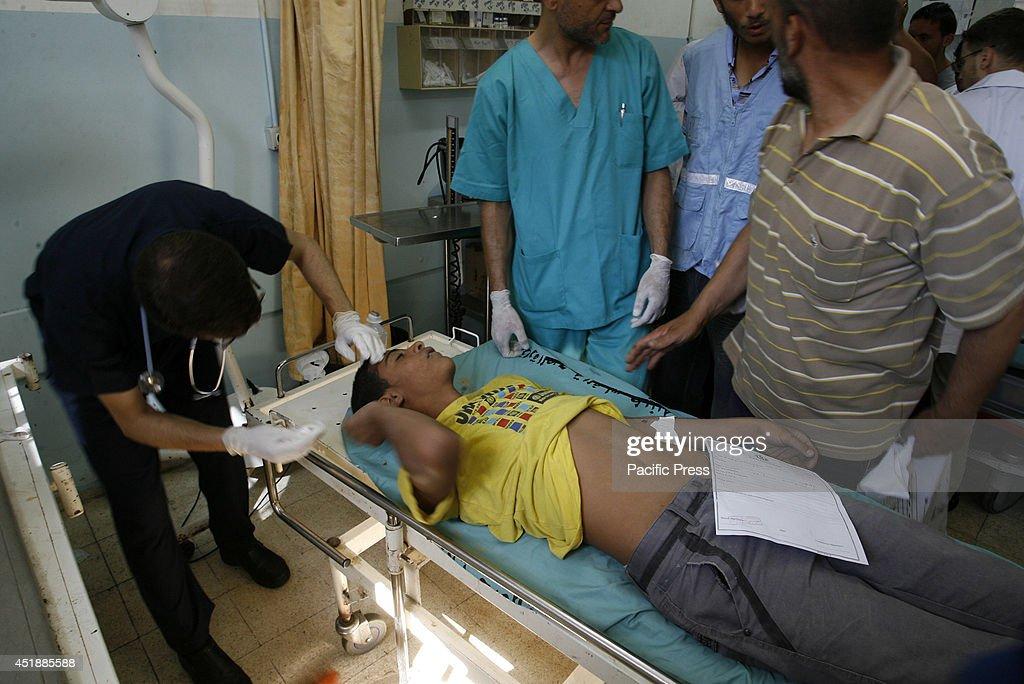 Palestinian men carry an injured person at Nasser Hospital... : ニュース写真