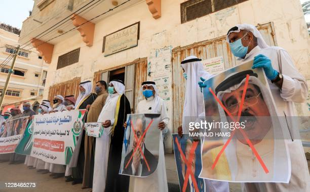 Palestinian men carry the exed out portraits of the Bahraini King US President and Israeli Premier during a protest in Deir alBalah in central Gaza...