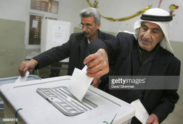 Palestinian men cast their ballots at a polling station January 25 2006 in Hawarra village in the West Bank Voters are choosing among 11 party lists...