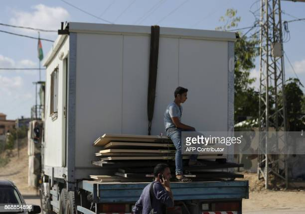 Palestinian men dismantle a structure held by the Islamist group Hamas at the northern entrance of the Gaza Strip just after the Israelicontrolled...