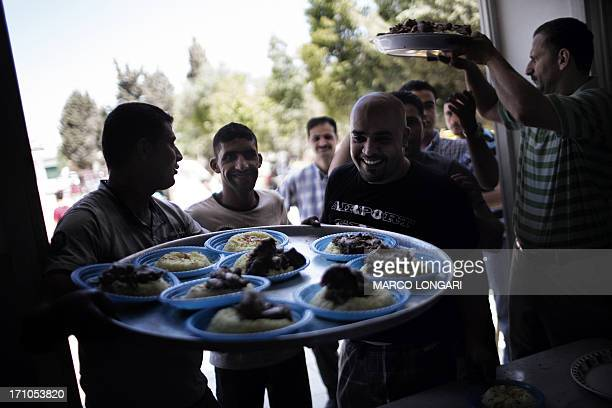 Palestinian men distribute plates of the traditional 'mansaf' dish during a mass wedding in the West Bank village of Silwad on June 21 2013 A total...