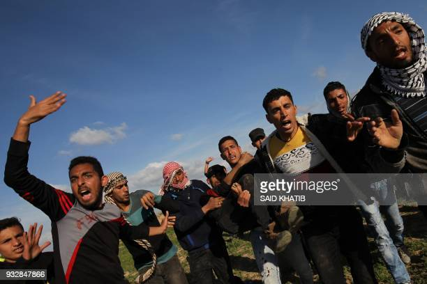 Palestinian men help evacuate an injured protester during clashes with Israeli troops near Khan Yunis by the border fence between Israel and the...