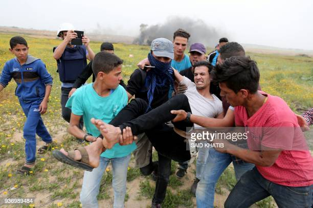 TOPSHOT Palestinian men help evacuate an injured protester during clashes with Israeli troops near Khan Yunis by the border fence between Israel and...