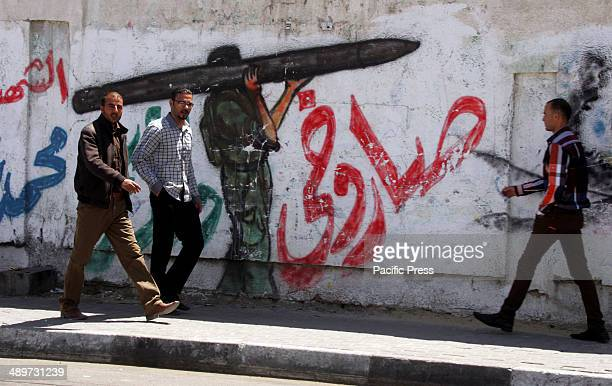 "Palestinian men, in Rafah in the southern Gaza Strip, walk next to a wall drawing/mural of a militant carrying a rocket. Nakba, or ""catastrophe"",..."