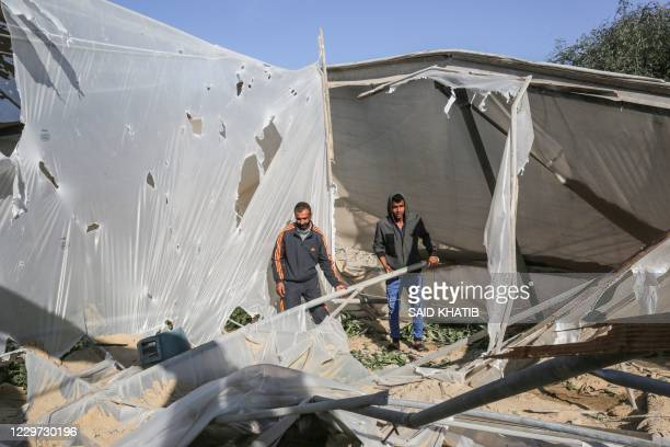 Palestinian men inspect the damage at the site of an Israeli air strike in Khan Yunis town the southern Gaza Strip November 22 2020 A rocket was...