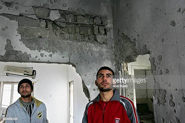 Palestinian men inspect the damage to the Ghazata Hashem charitable society building after it was hit by a missile from an Israeli helicopter early...