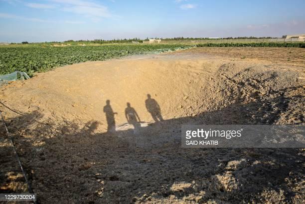 TOPSHOT Palestinian men look at a crater at the site of an Israeli air strike in Khan Yunis town the southern Gaza Strip November 22 2020 A rocket...