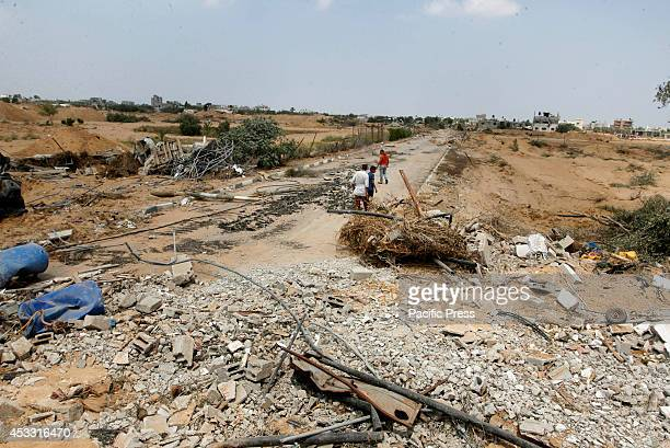 Palestinian men look at the destroyed tunnel connecting Gaza Strip and Israel, in the area of Rafah in the Southern Gaza Strip during the 72-hour...