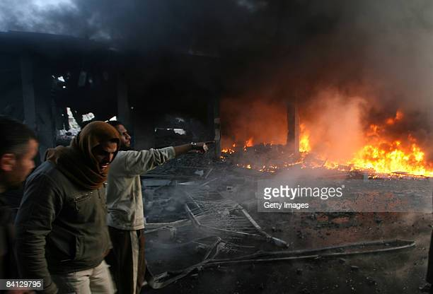 Palestinian men look on as flames rise from debris at the site of an Israeli air strike on December 28, 2008 in Rafah, Gaza. Israel has launched...