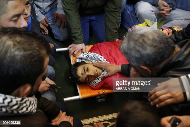 Palestinian men mourn over the body of Musab Firas alTamimi who was shot dead in clashes with the Israeli army a day earlier during his funeral in...