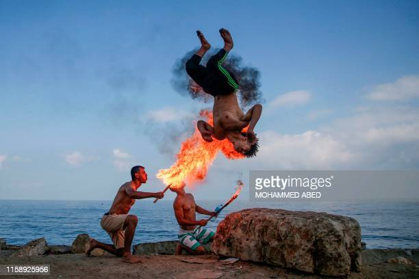 TOPSHOT Palestinian men perform fire breathing on the beach as an entertainment for children during the summer vacation in Gaza City on August 1 2019