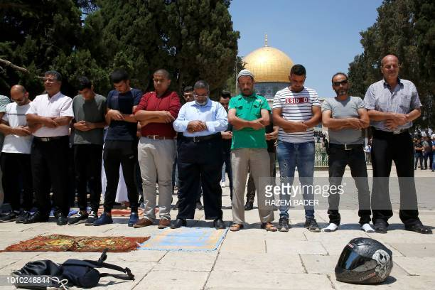 Palestinian men pray in front of the Dome of the Rock at the alAqsa mosque compound in the Jerusalem's Old City on August 03 2018