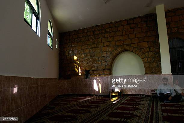 Palestinian men read the Koran at a mosque during the third day of the holy Muslim fasting month of Ramadan in the West Bank city of Ramallah 15...