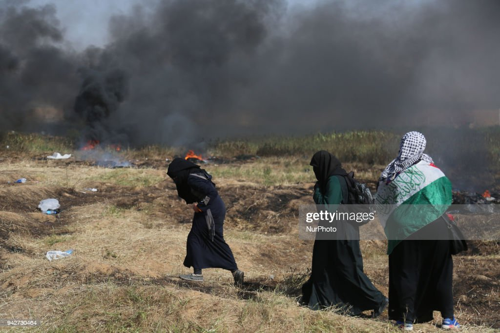 Palestinian men run for cover from tears gas canisters at the Israel-Gaza border during a protest, east of Gaza City in the Gaza strip, on April 6, 2018. Clashes erupted on the Gaza-Israel border on April 6, AFP journalists said, a week after similar demonstrations led to violence in which Israeli force killed 19 Palestinians, the bloodiest day since a 2014 war.