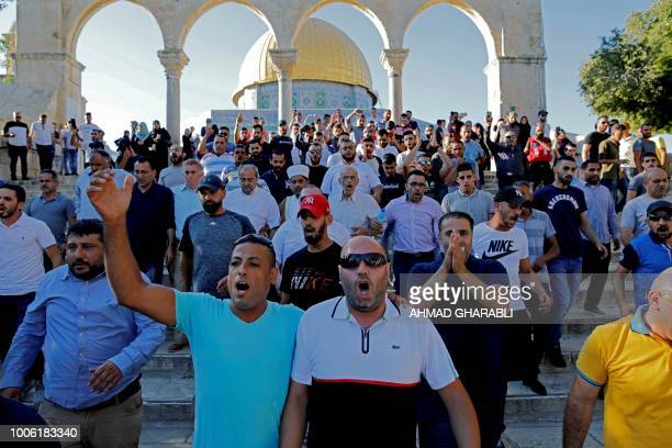 Palestinian men shout slogans in front of the Dome of the Rock at the alAqsa mosque compound in the Jerusalem's Old City on July 27 after the site...