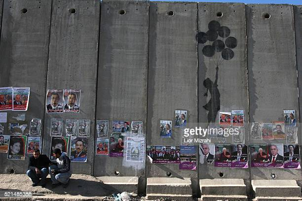 Palestinian men sits next to graffiti by the British artist Bansky and parliamentary election campaign posters on Israel's separation wall near the...