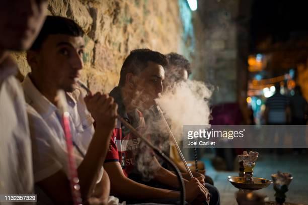 パレスチナ人男性がエルサレムのムスリム地区で nargila を喫煙 - 水キセル ストックフォトと画像