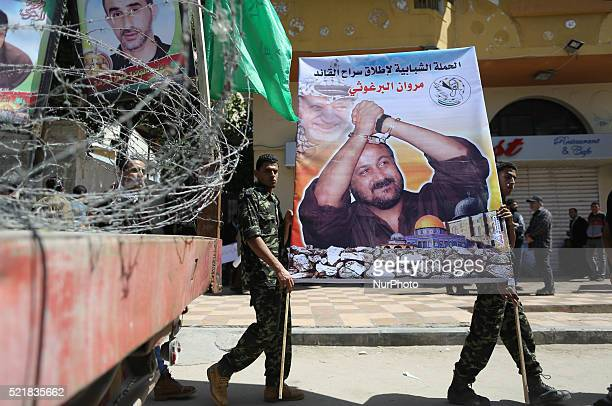Palestinian men take a poster bearing the portrait of jailed Fatah leader Marwan Barghuti during a rally marking Palestinian Prisoner Day in Gaza...