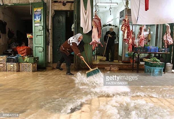 Palestinian men try to prevent flood water from entering shops in the old city of Hebron on November 27 2014 as a fierce winter storm which has been...