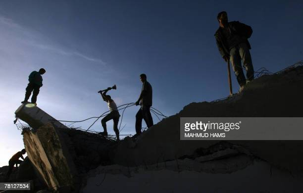 Palestinian men use sledgehammers to smash concrete and collect scrap iron from the wreckage of factories that were demolished by the Israeli army...