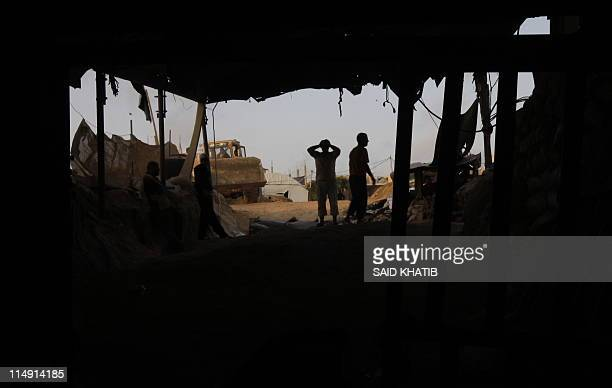 Palestinian men wait for sacks of gravel during a smuggling operation into the Gaza Strip through a tunnel under the EgyptGaza border in Rafah on May...