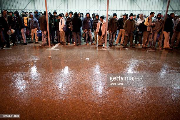 Palestinian men wait to be collected by their Israeli employers after crossing from the West Bank town of Qalqilya to work in the Jewish state in the...
