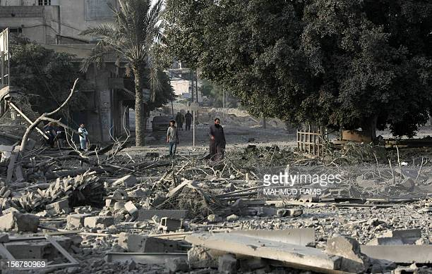 Palestinian men walk amidst debris at the destroyed compound of the internal security ministry in Gaza City after it was targeted by an Israeli air...