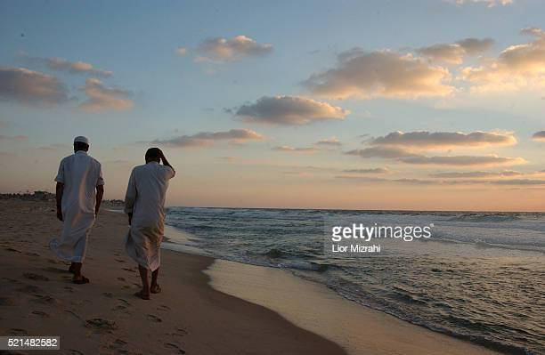 Palestinian men walk on the beach of the Gush Katif Settlement Block within the Gaza Strip Wednesday August 10 2005 Many Jewish families and business...