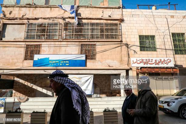Palestinian men walk past a building occupied by Israeli settlers bearing a sign reading in Hebrew Beit Rachel near the old city of the flashpoint...