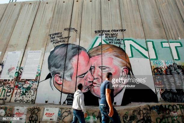 Palestinian men walk past a graffiti by street artist Lushsux depicting US President Donald Trump kissing Israeli Prime Minister Benjamin Netanyahu...