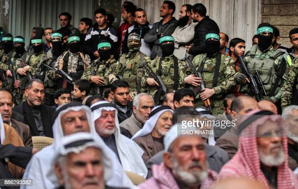 Palestinian men watch as fighters from the Ezzedine alQassam Brigades the armed wing of the Palestinian Hamas movement take part in a military show...