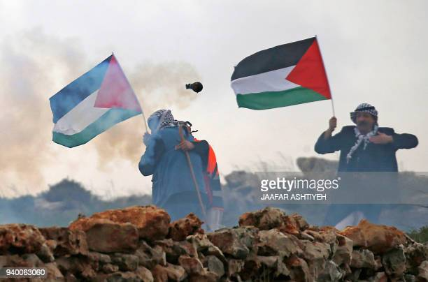 TOPSHOT Palestinian men wave their national flag during a demonstration commemorating Land Day in the village of Qusra in the Israeli occupied West...