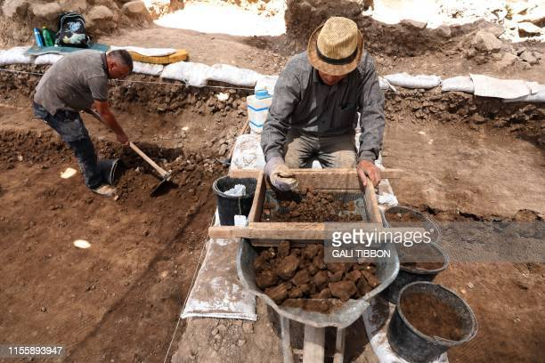 Palestinian men work on July 16 at the archeological excavation site of a settlement from the Neolithic Period discovered during archaeological...