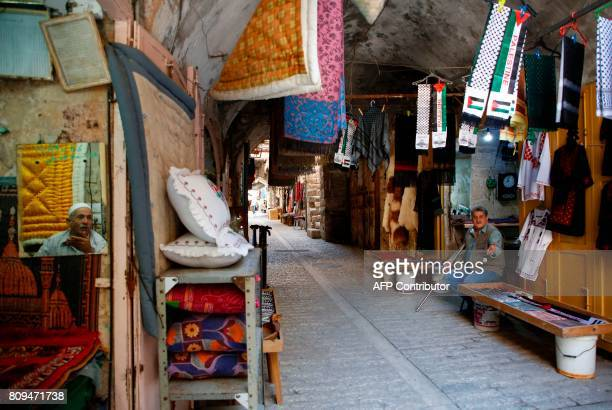 Palestinian merchants sit inside their stalls in the old market of the divided West Bank city of Hebron on June 29 2017 On July 7 2017 UNESCO...
