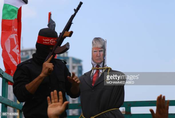 A Palestinian militant from the Popular Front for the Liberation of Palestine stands brandishing a weapon next to an effigy depicting US President...