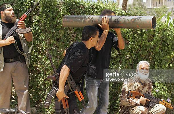 """Palestinian militant rests on his shoulder a home made type of """"rocket propelled grenade"""" he and others watch an on coming Israeli tank during armed..."""