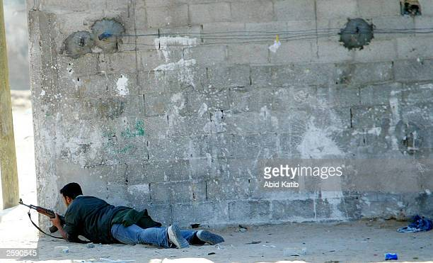 A Palestinian militant using an AK47 automatic rifle opens fire towards Israeli forces in the Al Salam area October 14 2003 in the Rafah refugee camp...